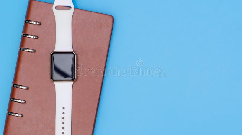 Den smarta klockan på anteckningsboken för organiserar begrepp på blått royaltyfri foto