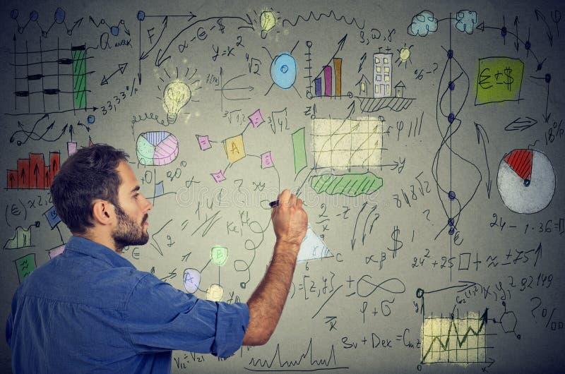 Den smarta mannen som analyserar människan, behöver att skriva självutveckling och affärsplan arkivbilder