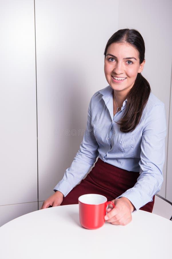 Den smarta professonalkvinnan har ett kaffeavbrott i kontoret royaltyfri bild