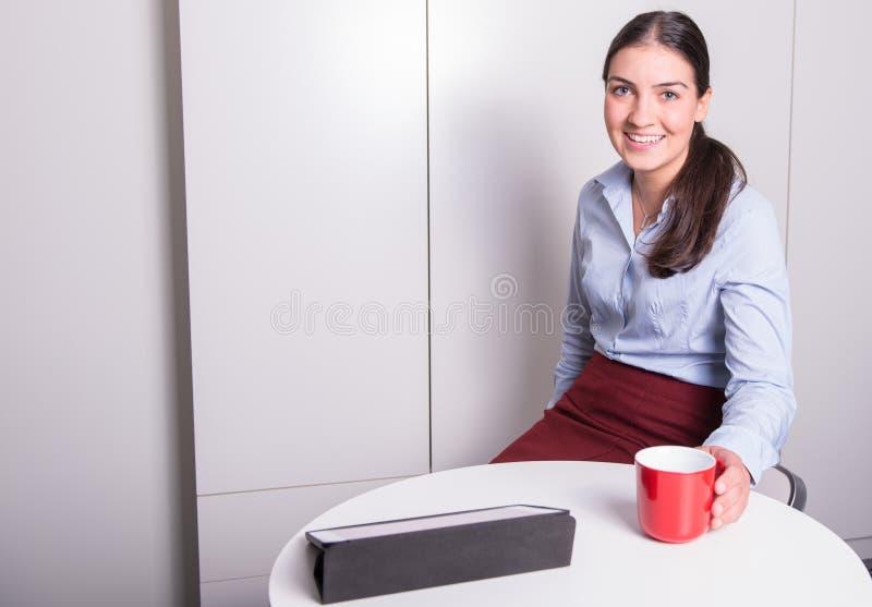 Den smarta professonalkvinnan har ett kaffeavbrott i kontoret arkivfoto