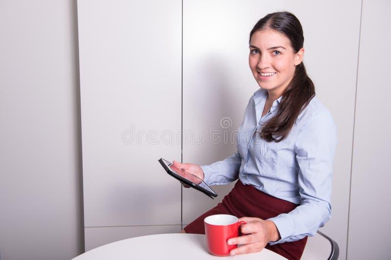 Den smarta professonalkvinnan ser på minnestavlan under kaffeavbrott royaltyfria bilder