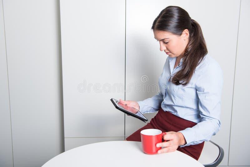 Den smarta professonalkvinnan ser på minnestavlan under kaffeavbrott royaltyfri fotografi