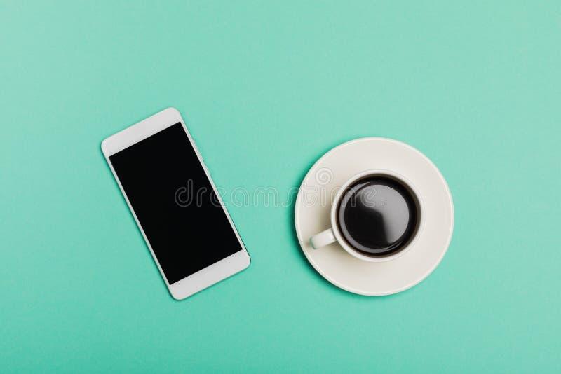 Den smarta telefonen och koppen kaffe på det blåa skrivbordet, den bästa sikten, lägenhet lägger royaltyfria bilder