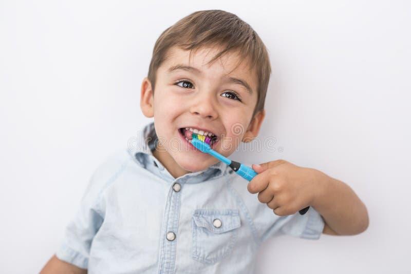 Den Smiley pojken gör ren tänder som isoleras på grå bakgrund royaltyfri fotografi