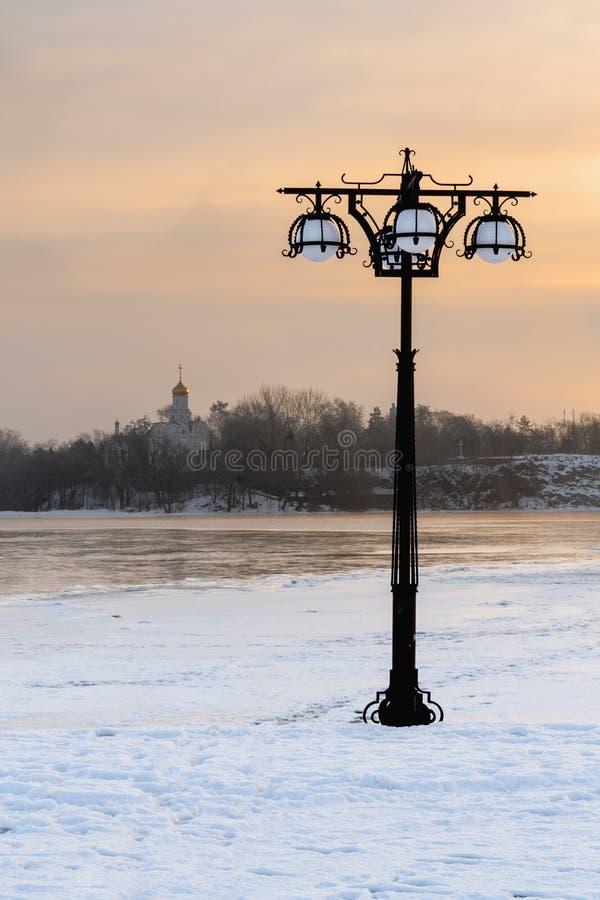 Den snöig invallningen längs den dimmiga floden med lyktor på den dimmiga soluppgången - övervintra landskapet iii. fotografering för bildbyråer