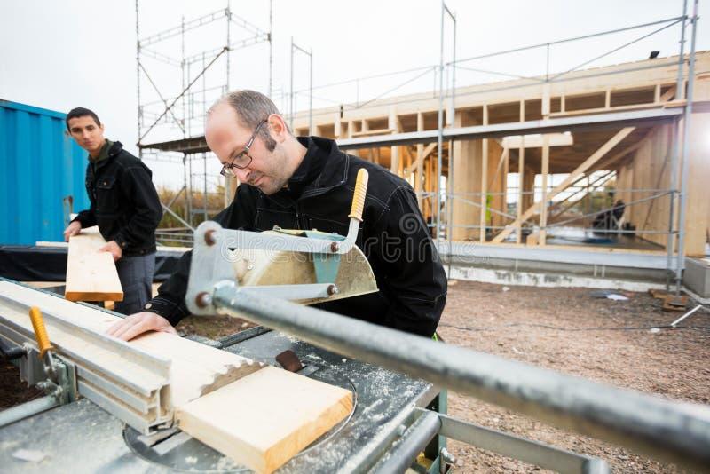 Den snickareCutting Wood Using tabellen såg medan att hjälpa för kollega fotografering för bildbyråer