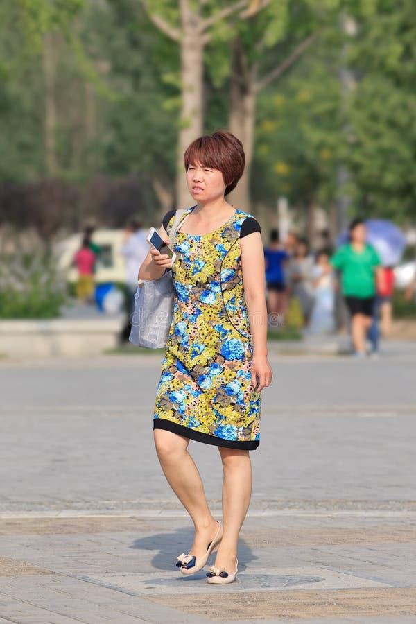 Den snygga medelåldersa kinesiska kvinnan går i en parkera, Peking, Kina royaltyfri bild