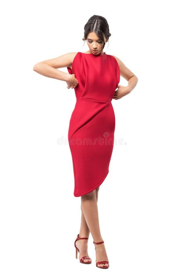 Den sofistikerade glamorösa kvinnan får klädd justera den röda eleganta aftonkappan arkivbilder