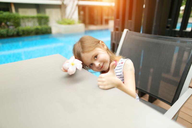 Den soliga ståenden av flickavisningen för den lilla ungen tummar upp eller som på simbassäng royaltyfri foto