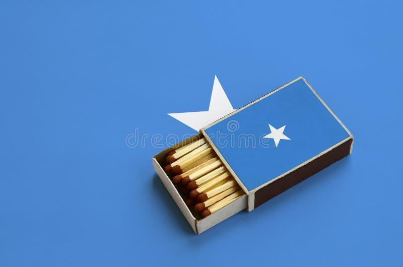 Den Somalia flaggan visas i en öppen tändsticksask, som fylls med matcher och ligger på en stor flagga arkivbild