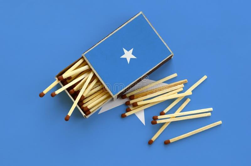 Den Somalia flaggan visas på en öppen tändsticksask, som flera matcher faller från och lögner på en stor flagga arkivfoton