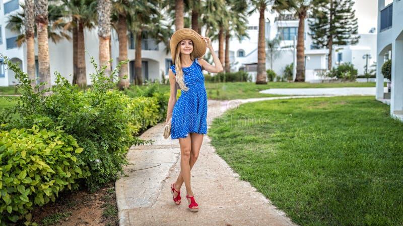In den Sommerferien steht ein angemessenes behaartes schönes junges nettes Mädchen auf einer Palmengasse an den Feiertagen lizenzfreie stockbilder