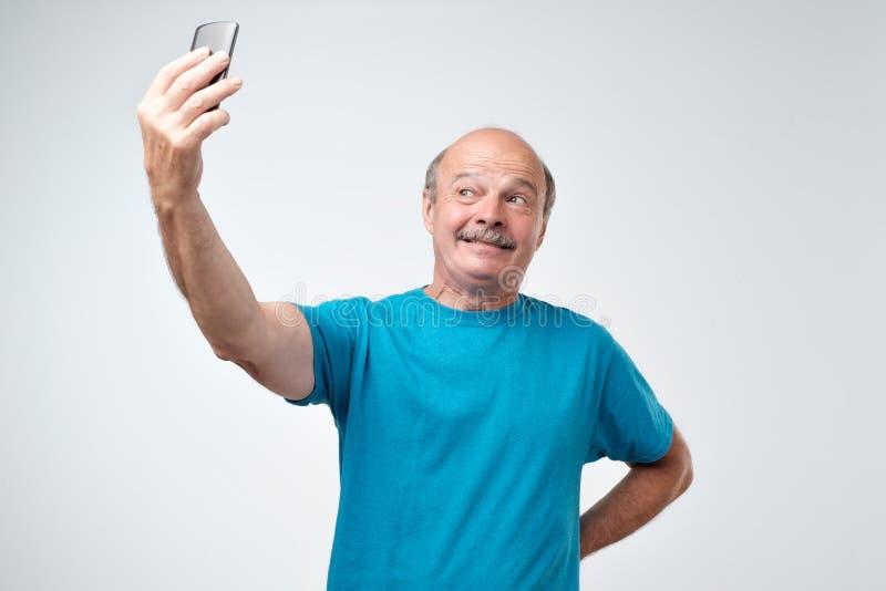 Den spännande höga mannen som använder mobiltelefonen, gör selfie royaltyfria foton