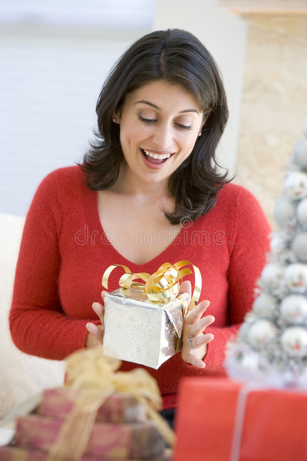 den spännande julen öppnar presenten till kvinnan royaltyfri bild