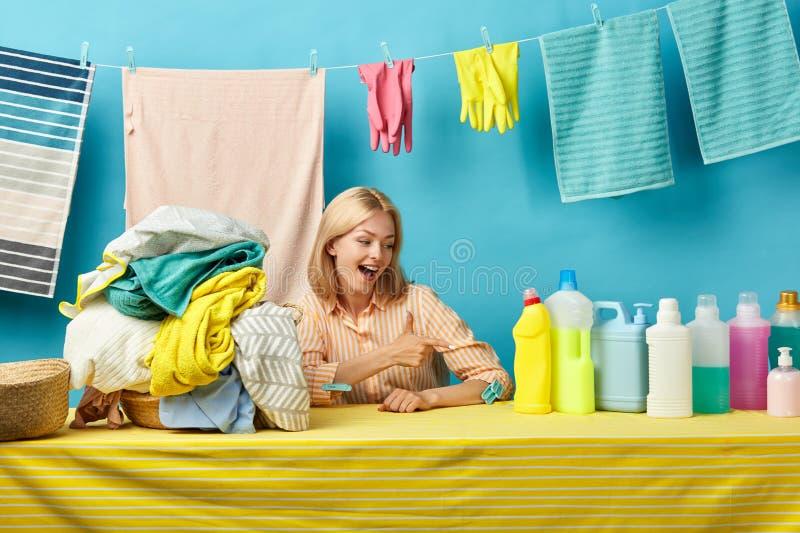 Den spännande positiva flickan indikerar på flaskor av tvättande tvål arkivbilder