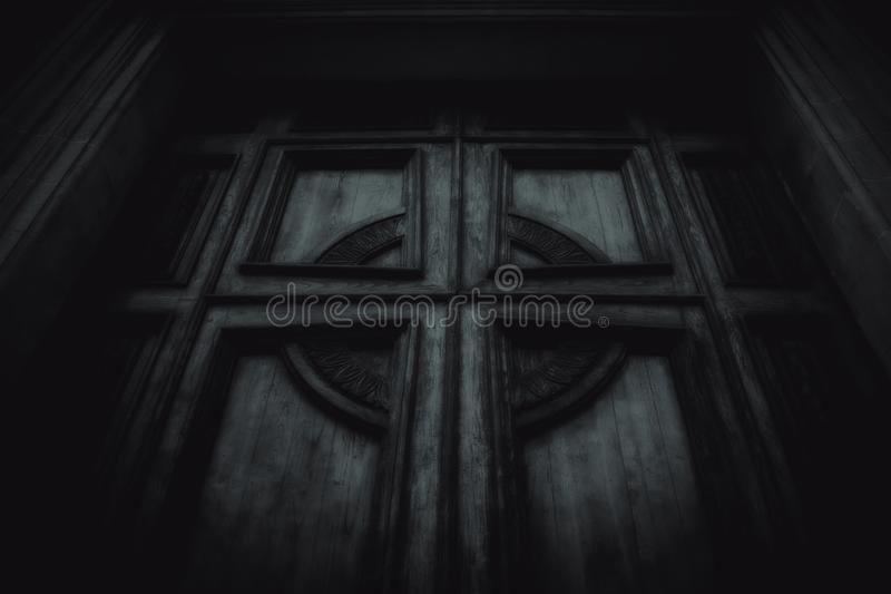 Den spöklika dörren med ett kors arkivbild