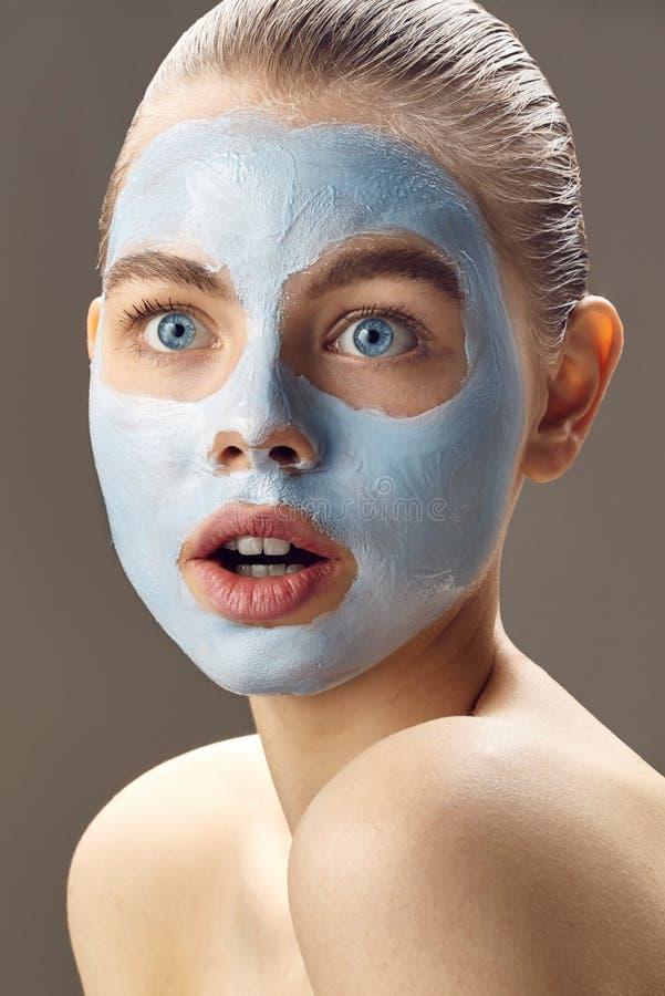 Den Spa kvinnan som applicerar maskeringen för framsida och, förvånas arkivbilder