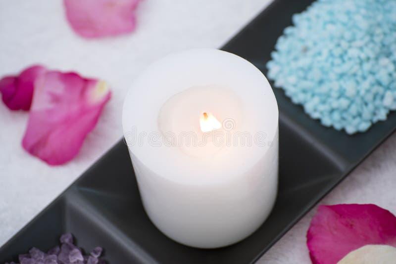 Den Spa tillbehören den aromatiska stearinljuset, blomman som är salt skurar arkivbild