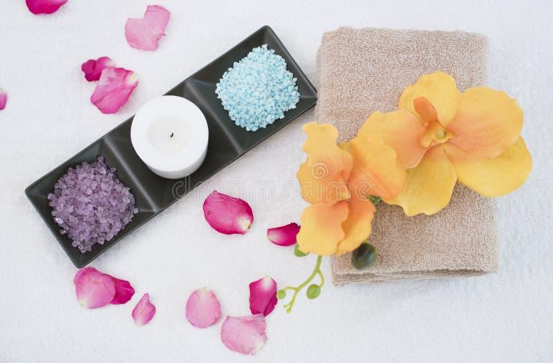 Den Spa tillbehören den aromatiska stearinljuset, orkidéblomman som är salt skurar arkivbild