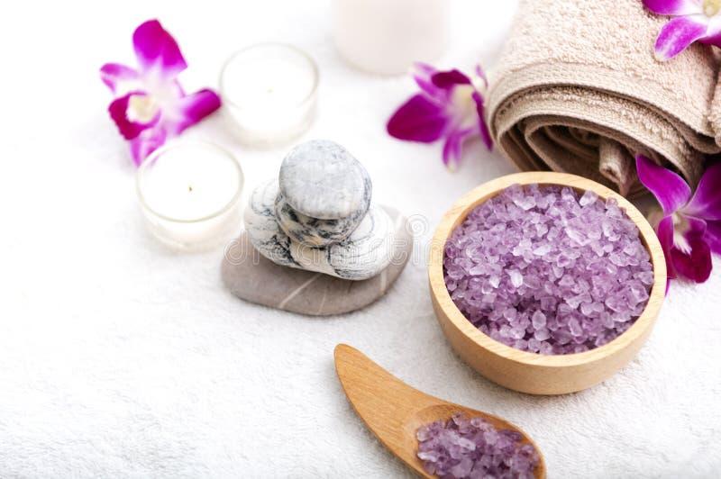 Den Spa tillbehören den aromatiska stearinljuset, orkidéblomman som är salt skurar och handduken arkivfoton