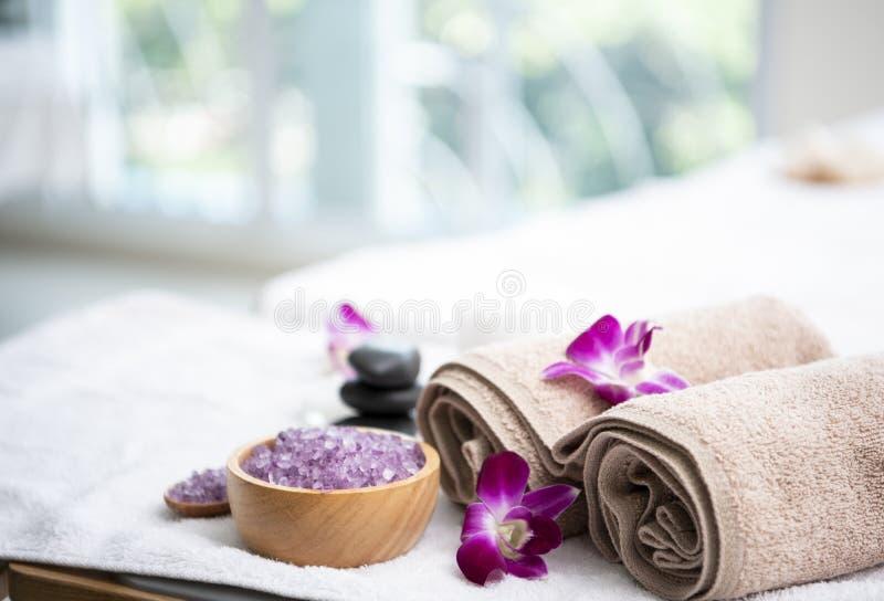 Den Spa tillbehören den aromatiska stearinljuset, orkidéblomman som är salt skurar och handduken royaltyfri fotografi
