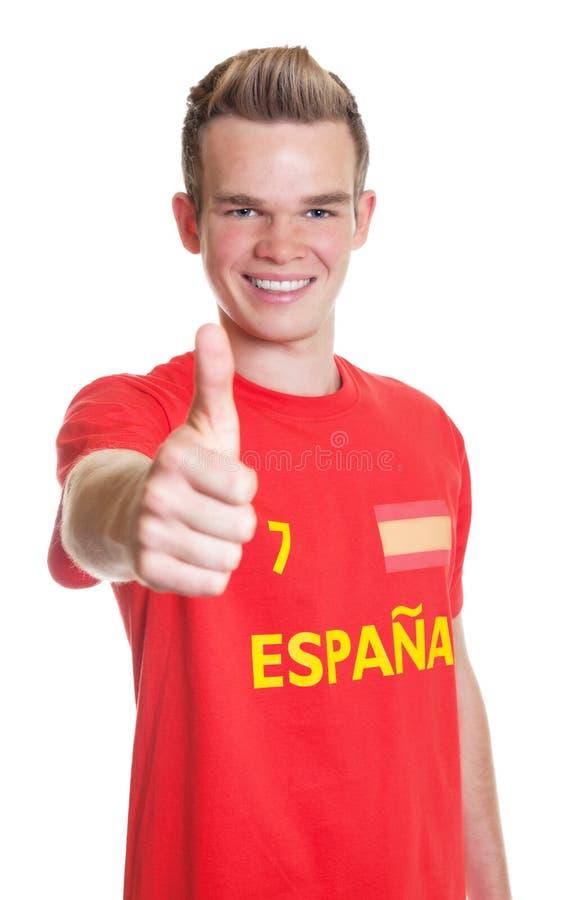 Den spanska sportfanen med visning för blont hår tummar upp arkivfoton