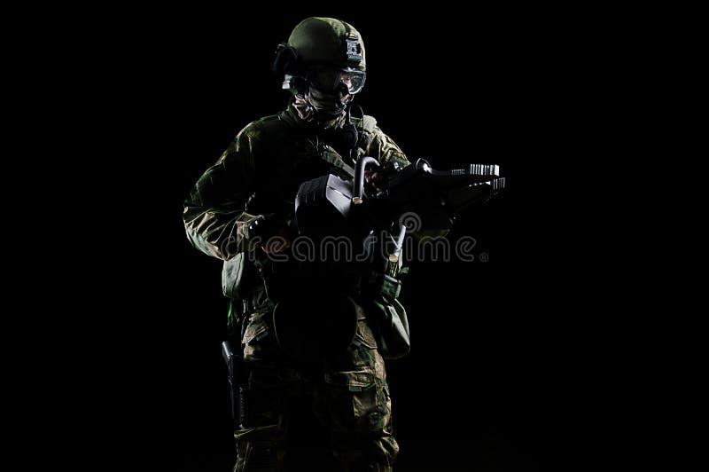 Den speciala gruppsoldaten rymmer en stålar för att öppna dörrarna royaltyfri bild