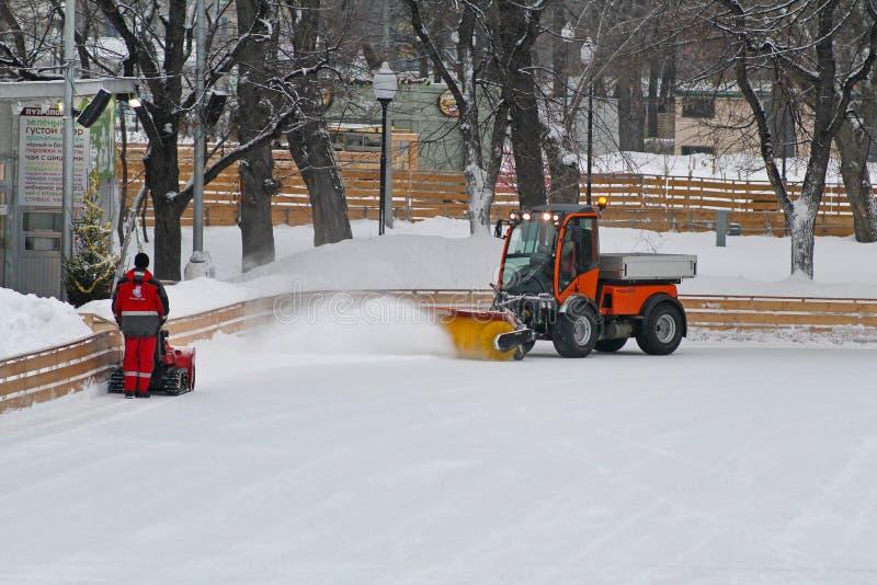 Den speciala maskinen och arbetaren gör ren skridskoåkningisbanan parkerar in Gorkogo i Moskva royaltyfri bild