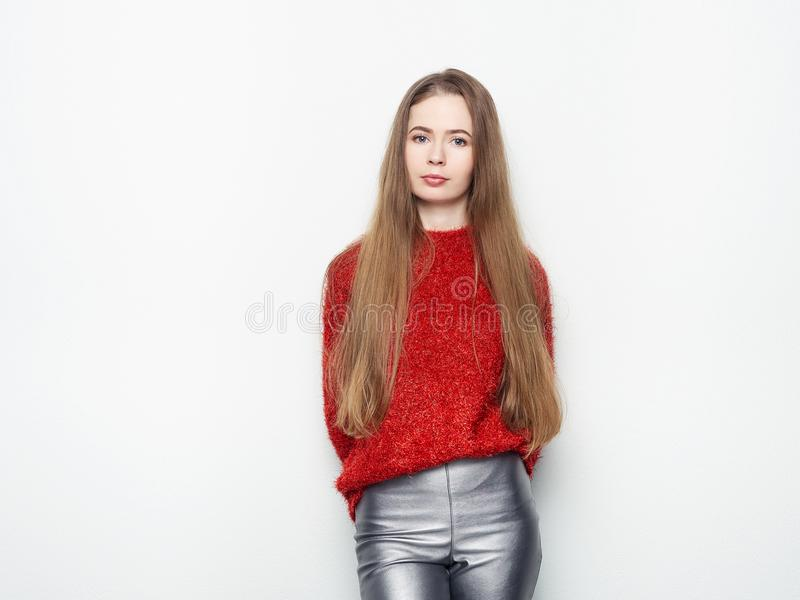 Den spektakulära blonda kvinnan i rött blussilverläder flåsar att posera framme av den vita väggen Ursnyggt långt hår för behagfu royaltyfri bild