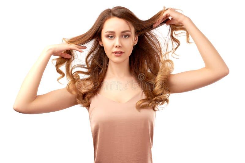 Den spektakul?ra unga brunettflickan rymmer hennes krullning med h?nder och ser expressively kameran royaltyfria bilder