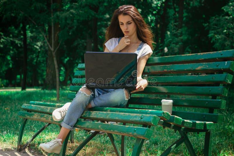Den spensliga brunetten sitter på en bänk i parkera och skrivar ut på en bärbar dator fotografering för bildbyråer