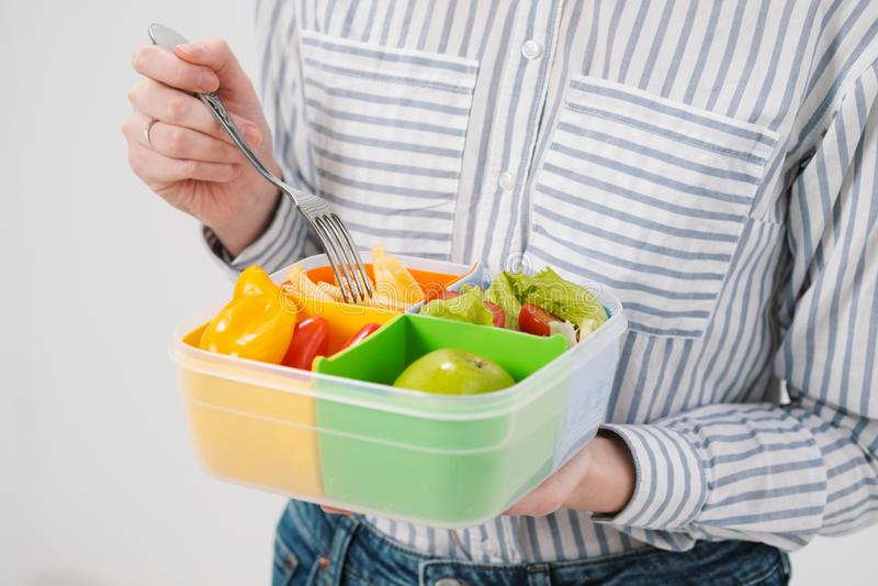Den spensliga brunettflickan med långt hår på en vit bakgrund äter med en gaffel från en behållare för luncher Färgask för royaltyfri fotografi