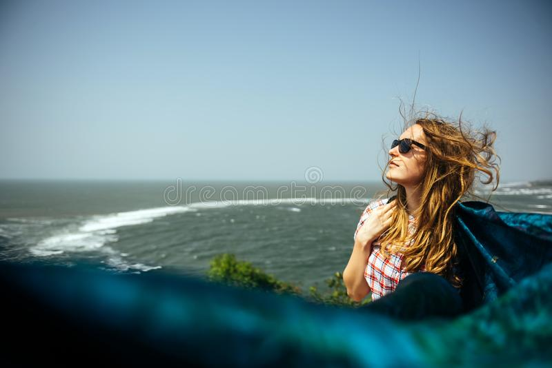 Den spensliga härliga kvinnaflickan på havet vaggar med pareosjalen royaltyfria bilder