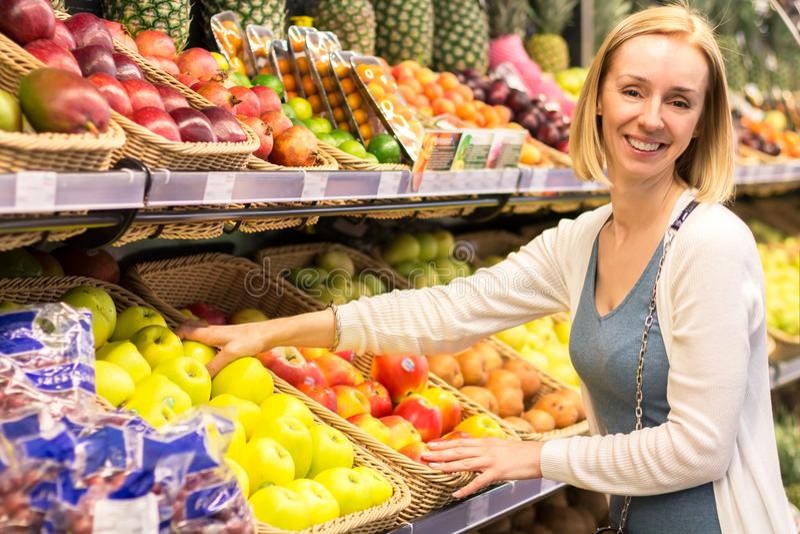 Den spensliga kvinnablondinen väljer frukter i lagret arkivfoto
