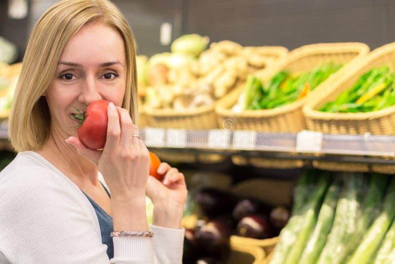 Den spensliga kvinnablondinen väljer grönsaker i lagret fotografering för bildbyråer