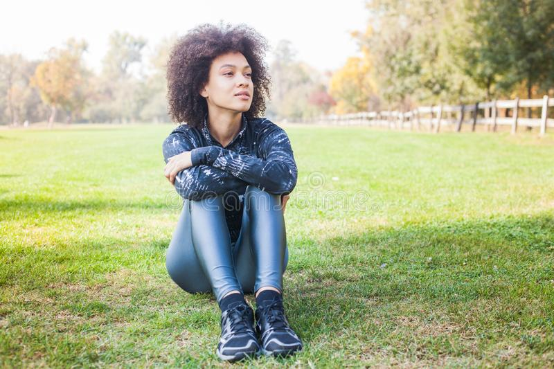 Den sportiga afro- amerikanska unga kvinnan kopplar av på grönt gräs på parkerar arkivfoto