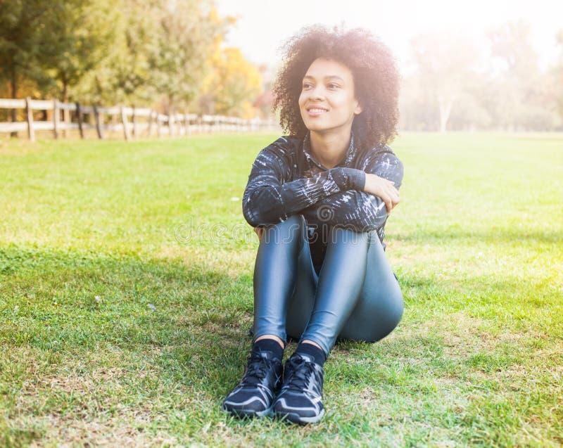 Den sportiga afro- amerikanska unga kvinnan kopplar av på grönt gräs på parkerar royaltyfri fotografi