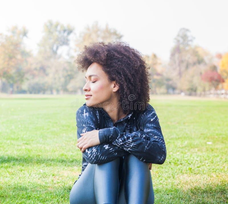 Den sportiga afro- amerikanska unga kvinnan kopplar av på grönt gräs på parkerar royaltyfri bild