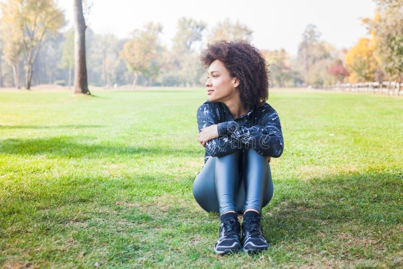 Den sportiga afro- amerikanska unga kvinnan kopplar av på grönt gräs på parkerar royaltyfria bilder