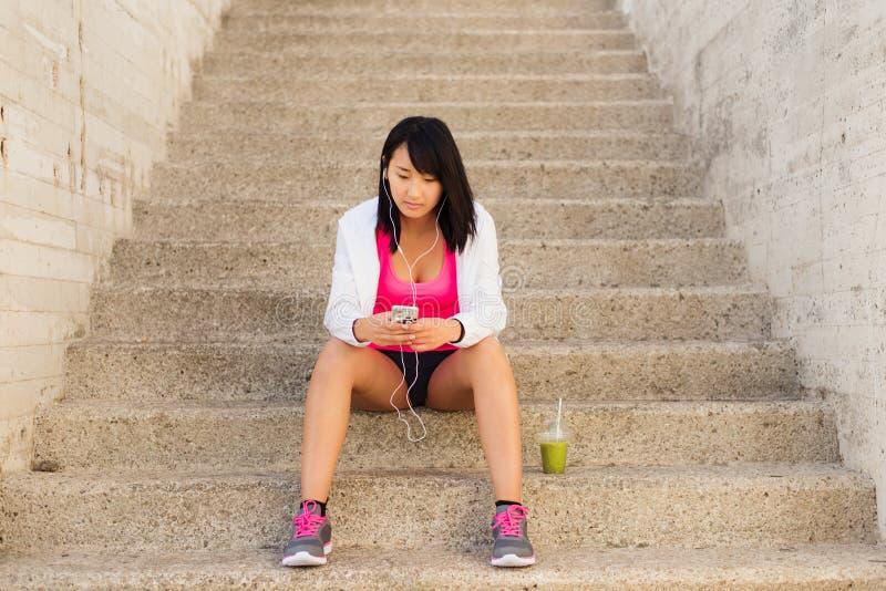 Den sportiga asiatiska kvinnan som tar en genomkörare, vilar med smartphonen royaltyfria foton