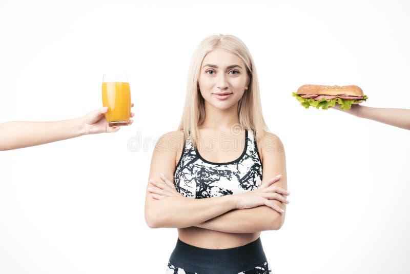 Den sportiga blondinen rymmer i hennes hand en hamburgare och ett exponeringsglas av ny fruktsaft arkivfoton