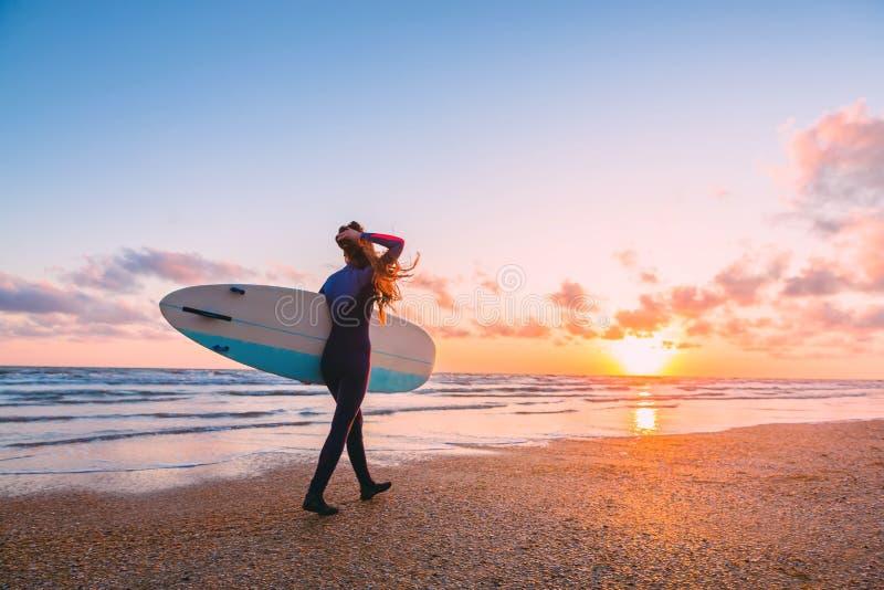 Den sportiga bränningflickan går till att surfa Kvinna med surfingbrädan och solnedgång eller soluppgång på havet royaltyfria bilder