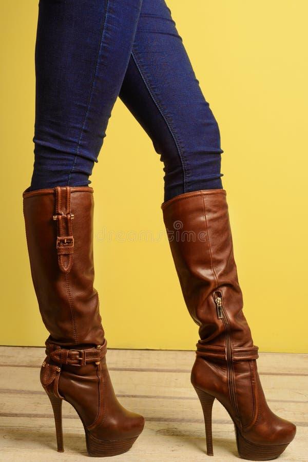 Den sportiga flickan i brunt hög-heeled kängor och jeans arkivbild