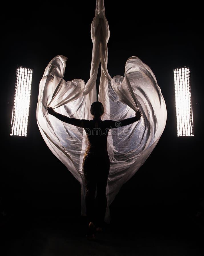 Den sportiga flickan i en Bourgognedräkt utför gymnastiska och cirkusövningar på vitt silke, i det contra ljuset royaltyfri fotografi