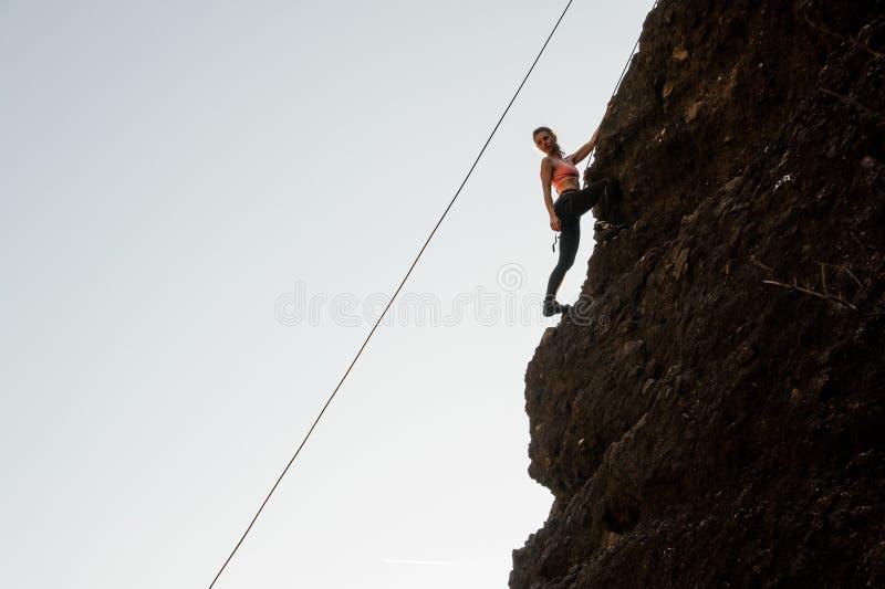 Den sportiga flickan som utrustas med ett rep som klättrar på slutta, vaggar och att se ner fotografering för bildbyråer