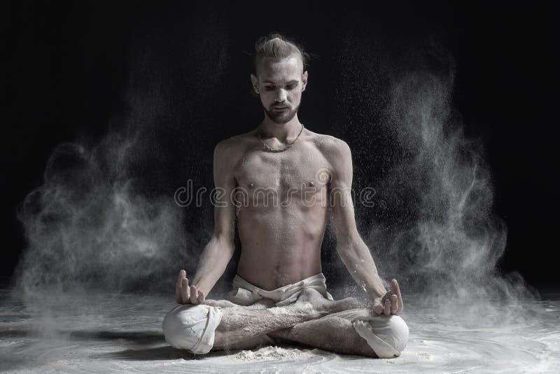 Den sportiga fridfulla unga mannen som mediterar sammanträde i kors-lagd benen på ryggen yogalotusblomma, poserar, Padmasana med  arkivfoton