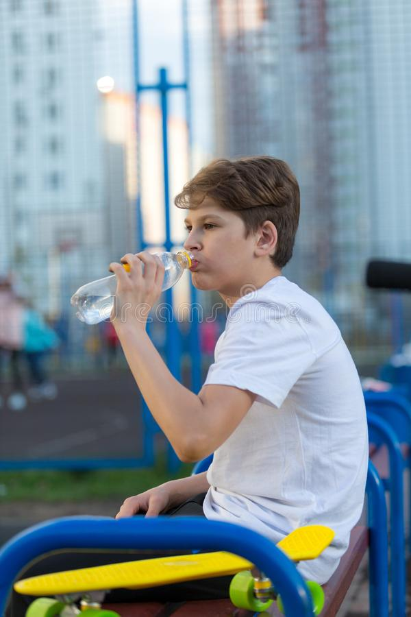 Den sportiga gulliga pojken dricker vatten, når han har spelat basket på sportjordningen Sund livsstil royaltyfri foto