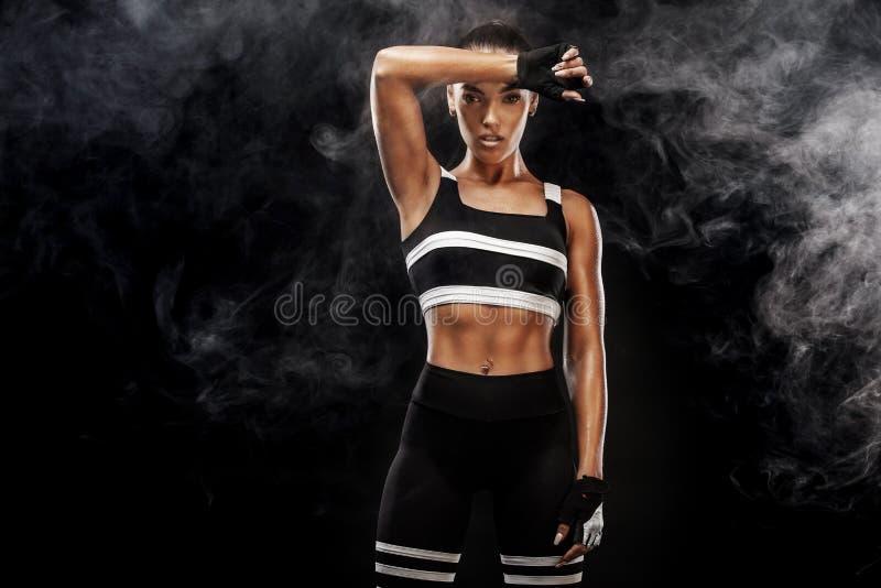 Den sportiga härliga afro--amerikanen modellen, kvinnan i sportwear gör kondition som övar på svart bakgrund för att bli färdig arkivbilder