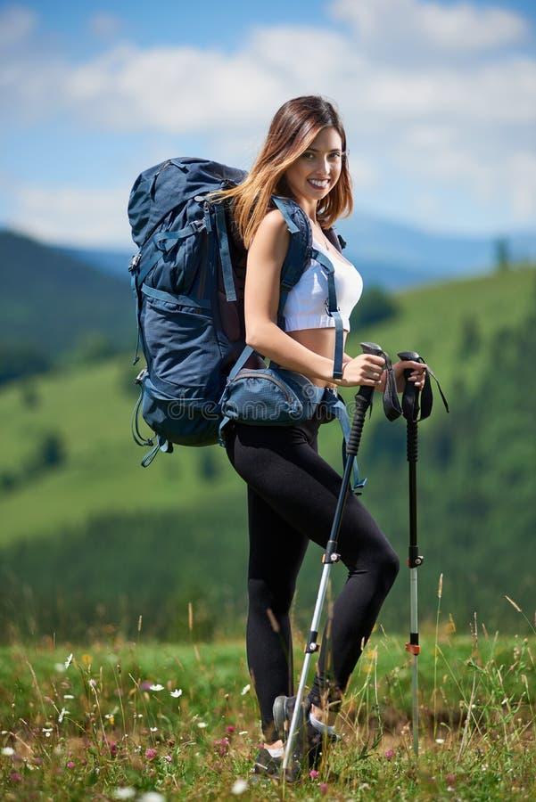 Den sportiga kvinnafotvandraren med ryggsäcken och trekking klibbar att fotvandra i bergen royaltyfri bild
