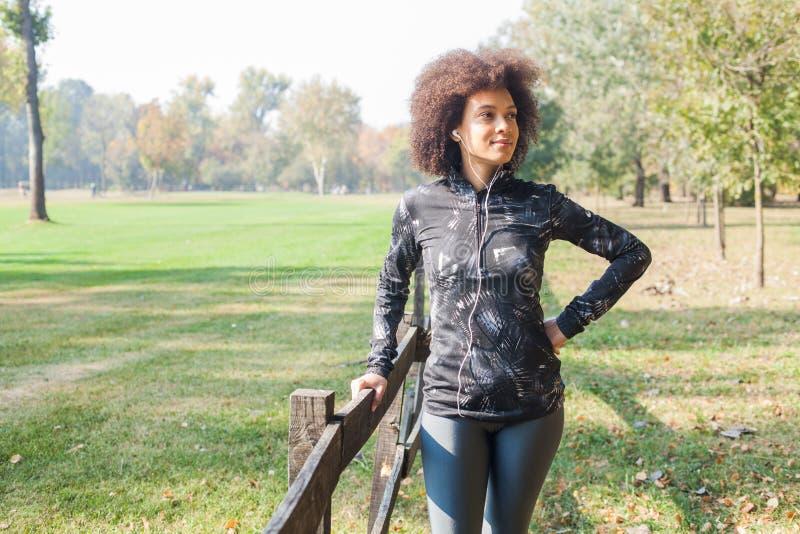 Den sportiga kvinnan kopplar av efter utbildande lyssnande musik på parkerar royaltyfria bilder
